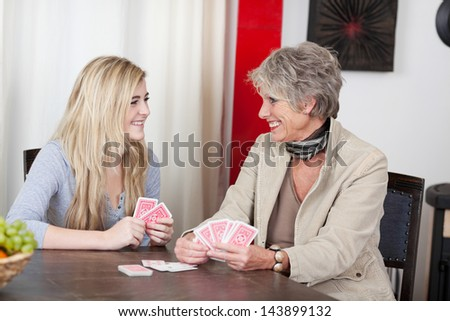 Image of a grandmother playing cards with her granddaughter and having fun. - stock photo