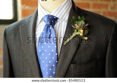 Image of a gray suit with blue tie and boutonniere - stock photo