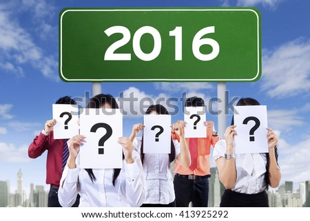 Image of a green road sign with number 2016 and unknown people holding question mark - stock photo