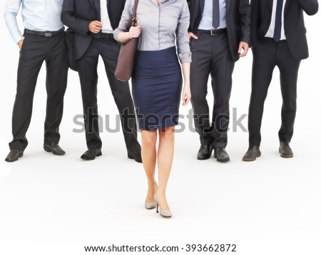 Image of a group of young businessmen standing with a businesswoman walking in front. Leading the way, diversity or harassment concept. Photo realistic 3d model scene. - stock photo