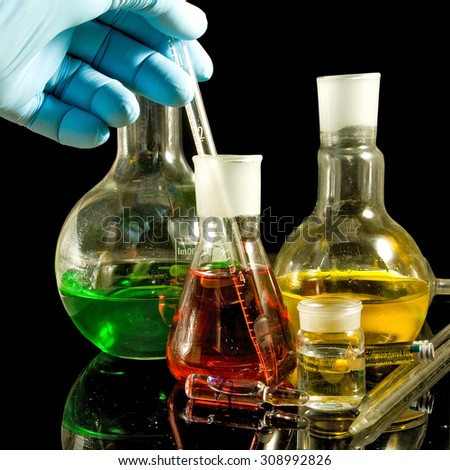 image of a hand in a glove and laboratory glassware closeup