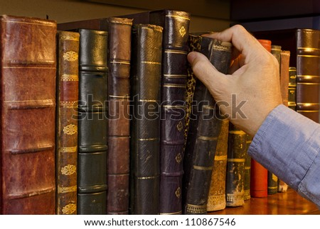 Image of a hand selecting a old book from a bookshelf - stock photo