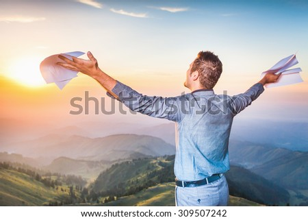 Image of a happy successful businessman who standing on the top of mountain and holding document paper. He looks into distance, thinking about future plans. Concept of professional career - stock photo