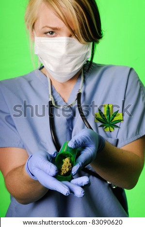 Image of a healthcare professional wearing surgical scrubs, stethoscope and mask holding a prescription bottle with marijuana inside on a chroma key background
