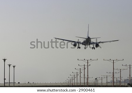 Image of a jet plane landing with landing gears down from behind