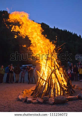 Image of a large campfire, around which people basking in the mountains at night - stock photo