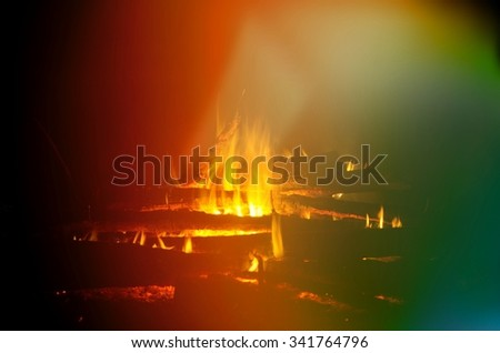 Image of a large campfire in the mountains at night - stock photo