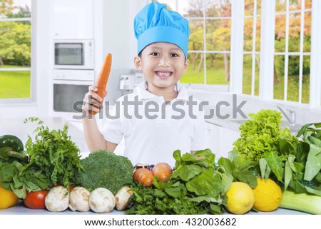 Image of a little Asian boy holding a carrot while preparing vegetables and wearing a cooking hat in the kitchen - stock photo