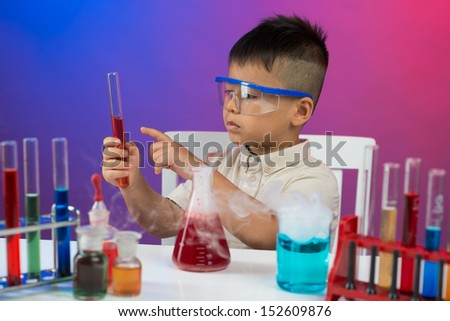 Image of a little boy concentrated on a chemical experiment in the lab