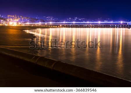 Image of a long exposure in Santa Barbara Harbor California during nighttime with famous Stearns Wharf lining the horizon - stock photo