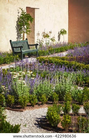 Image of a lush walled garden with landscaped paths. - stock photo