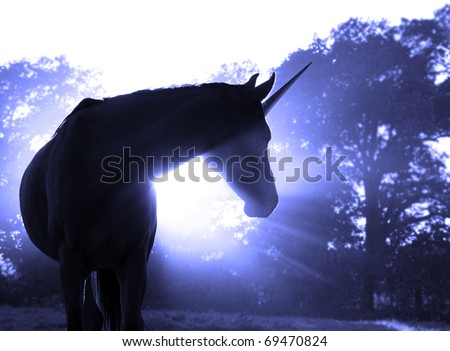 Image of a magical unicorn against hazy sunrise with sun rays