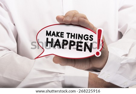 Image of a man hand holding speech balloon with the text make things happen, white shirt. Concept for motivation and goal achievement. - stock photo