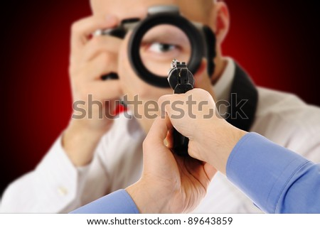 image of a man holding a gun and photographer - stock photo