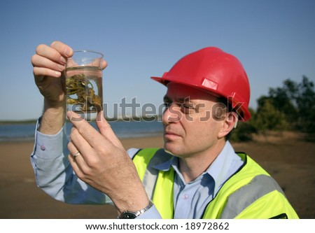 Image of a man holding on to a glass beaker with an environmental sample - stock photo