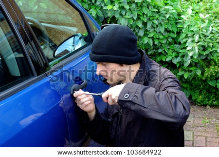 Image of a man stealing a car - stock photo