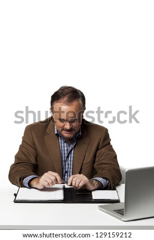 Image of a mature businessman looking at a folder on his desk