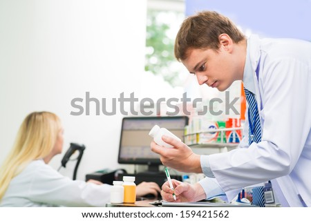Image of a medical intern holding a bottle of pills and writing something while working in the drugstore on the foreground - stock photo