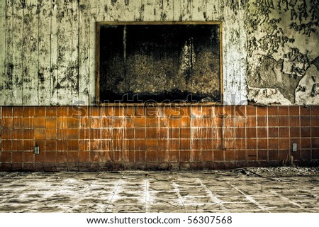 Image of a moldy black corkboard in a derelict abandoned building on a wall with peeling paint and scratched tile. - stock photo
