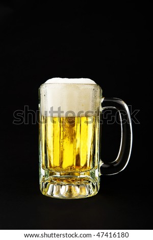Image of a mug of beer on black background - stock photo