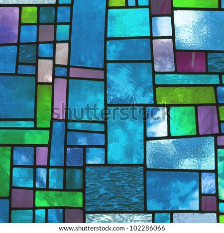 Image of a multicolored stained glass window with irregular block pattern in a hue of blue, square format - stock photo