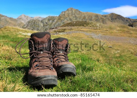 Image of a pair of hiking boots lying in the grass in front of a beautiful mountainous landscape in Pyrenees Mountains. - stock photo