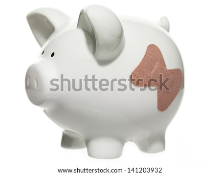 Image of a piggy bank with bandage over white background.