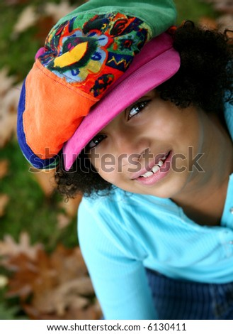 image of a pretty biracial girl in a funky hat....outdoor setting - stock photo