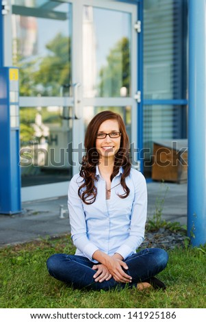 Image of a pretty woman sitting crosslegged in the lawn outside her house. - stock photo