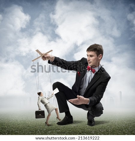 image of a puppeteer holds the puppet business woman - stock photo