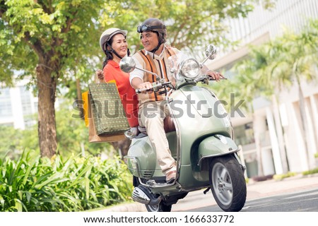 Image of a senior couple on a scooter where a wife with shopping bags  - stock photo