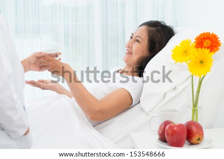 Image of a senior patient taking pills on the foreground - stock photo