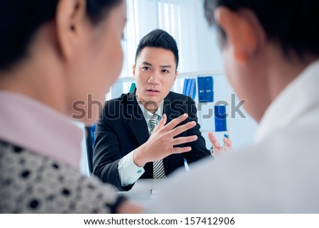 Image of a serious financial expert explaining something to his clients on the foreground - stock photo