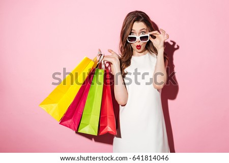 Image of a shocked young brunette lady in white summer dress wearing sunglasses posing with shopping bags and looking at camera over pink background.