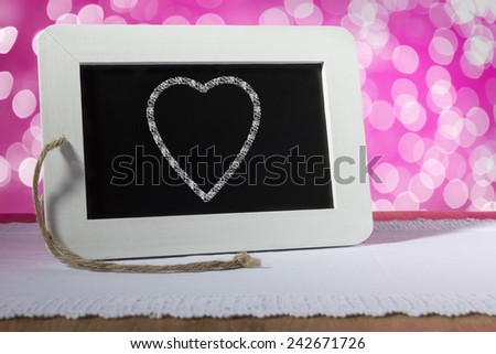 Image of a slate blackboard with chalk heart on pink background - stock photo