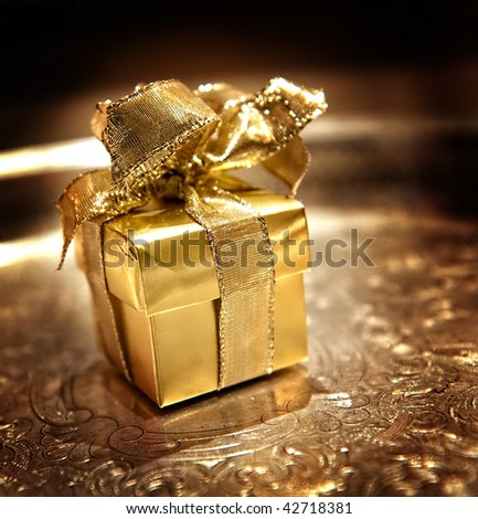 Image of a small gold gift wrapped box with ribbon on a silver tray - stock photo