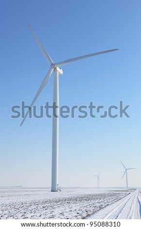 Image of a small road between  wind turbines in a plain covered by snow in winter. - stock photo