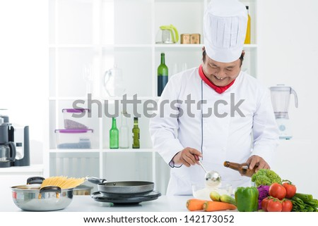 Image of a smiling cook preparing food in the kitchen - stock photo