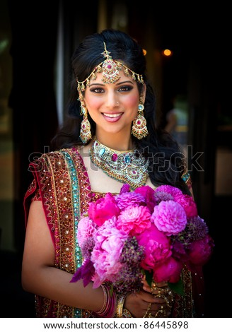 Image of a smiling Indian bride holding bouquet - stock photo