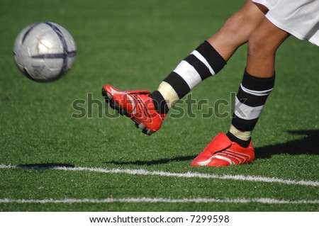 Image of a soccer player kicking the ball - stock photo