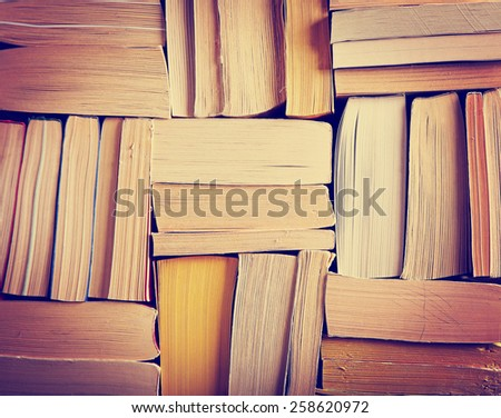 image of a stack of paperback books on the end of the pages toned with a retro vintage warm instagram like filter app or action effect - stock photo