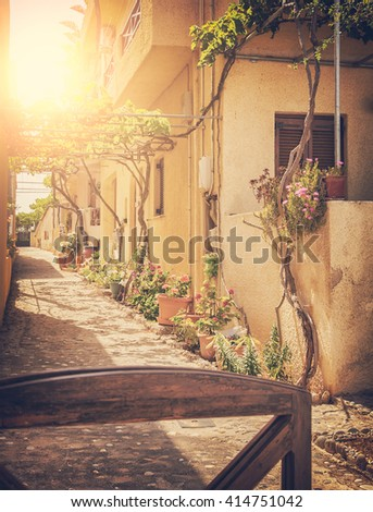 Image of a sunlit village street. Crete, Greece. Vintage styled.  - stock photo