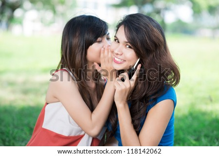 Image of a teenage girl sharing secret with her friend who talks over the phone - stock photo