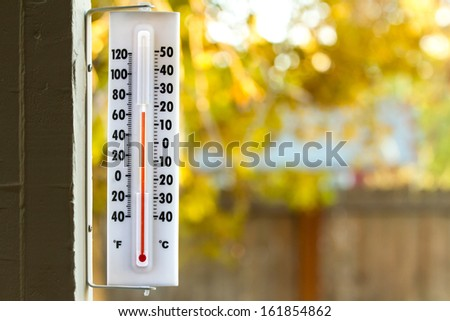 Image of a thermometer with pretty colors of fall in the background - stock photo