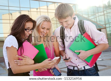 Image of a three young people looking at the cellphones - stock photo