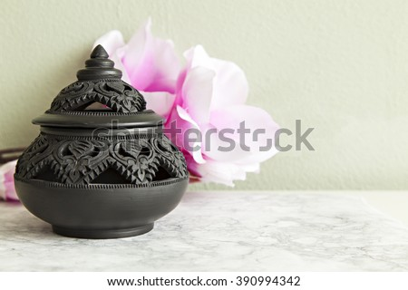 Image of a traditional clay pot from Thailand, with decorative carvings.  - stock photo