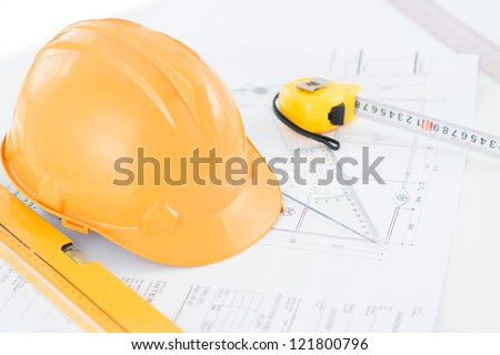 Image of a typical engineer workplace with blueprint, hardhat and measuring tools - stock photo