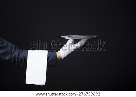 Image of a waiter hand holding a tray on dark background - stock photo