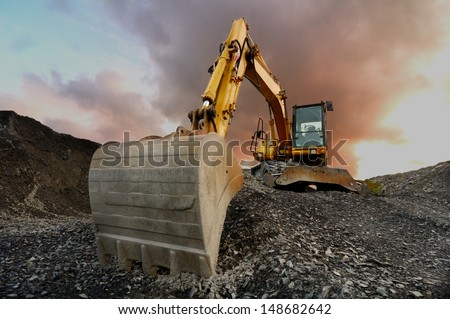 Image of a wheeled excavator on a quarry tip - stock photo