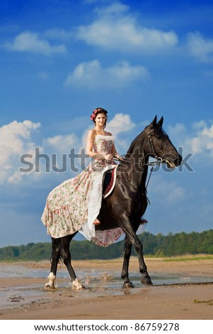 Image of a woman on a horse by the sea